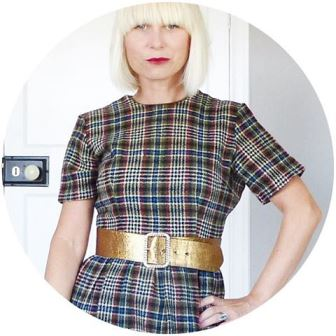 Kate Beavis wearing a vintage autumnal dress ad gold belt